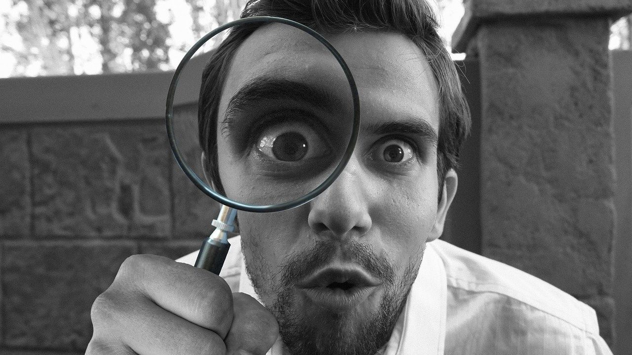 何かを虫眼鏡で調べている男性