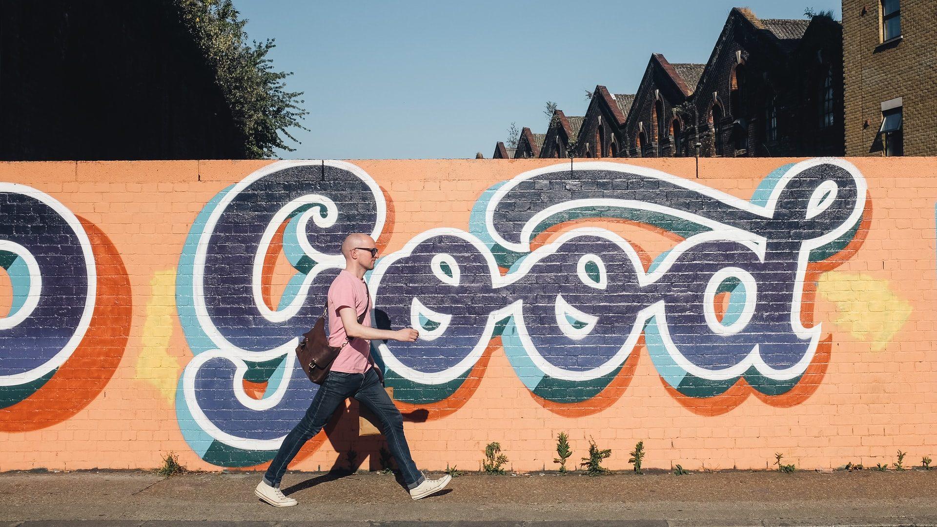 「GOOD」の壁紙の横を男性が歩いている